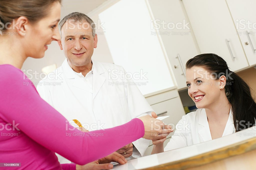 A woman serving customers at a reception at a clinic  royalty-free stock photo
