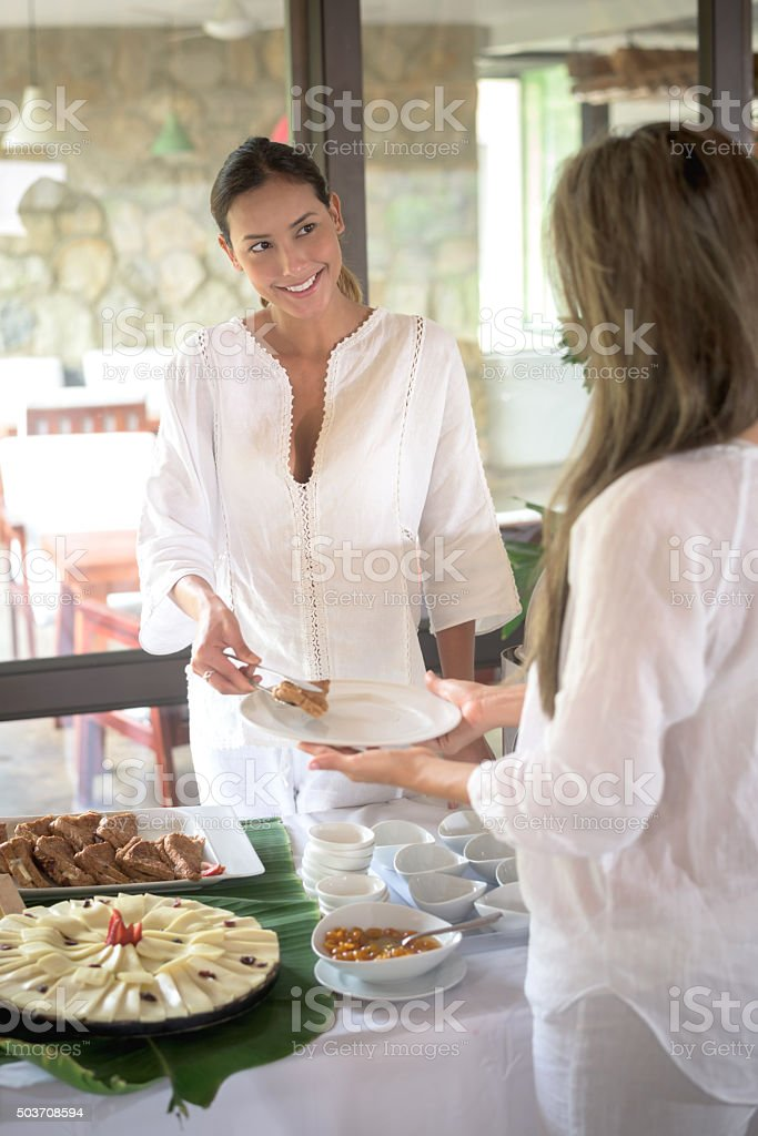 Woman serving food at a buffet stock photo