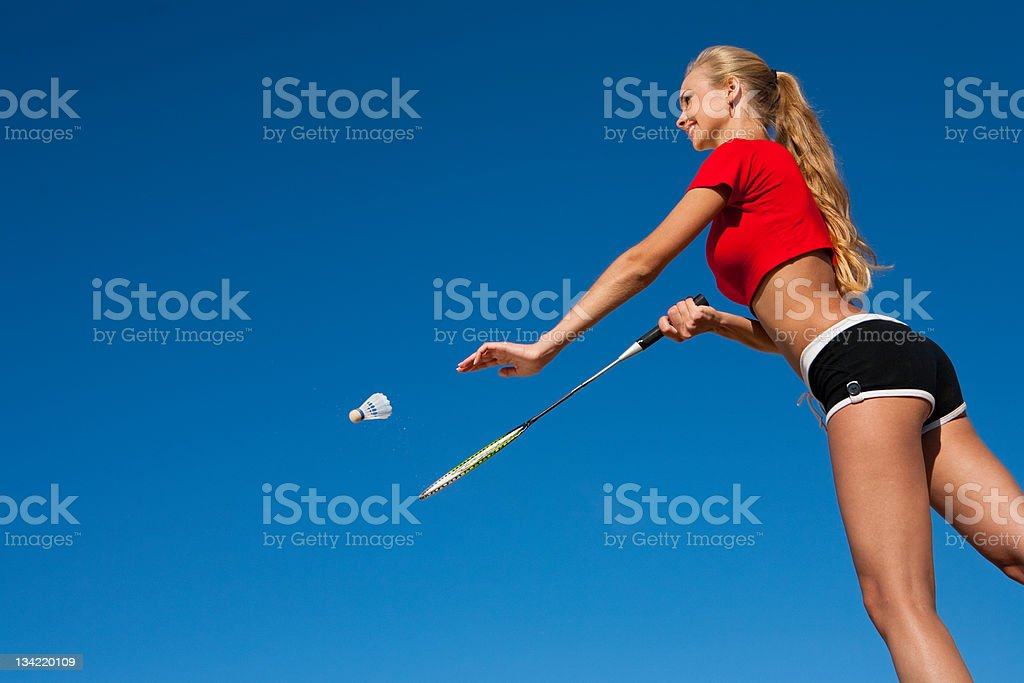 A woman serving in a game of badminton royalty-free stock photo
