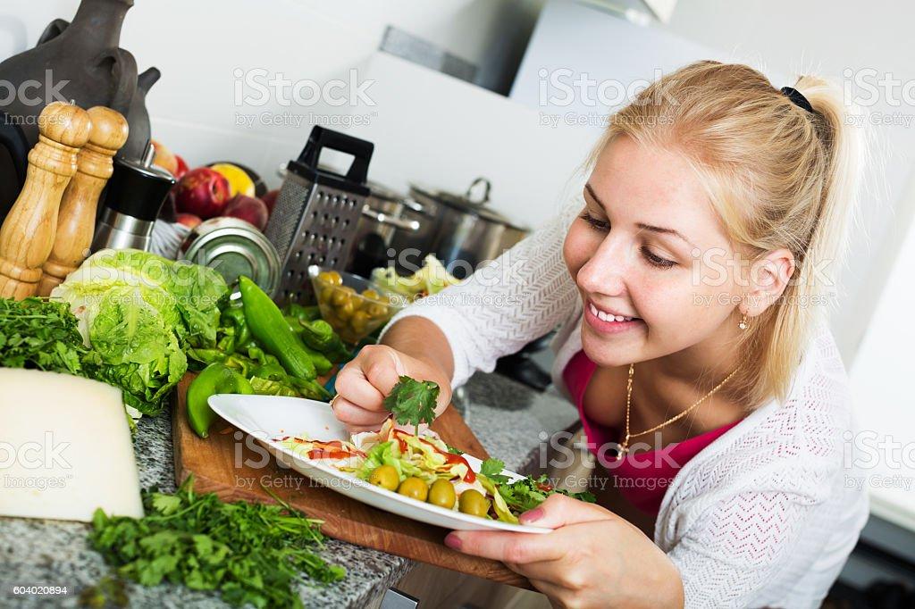 Woman serving salad on kitchen stock photo