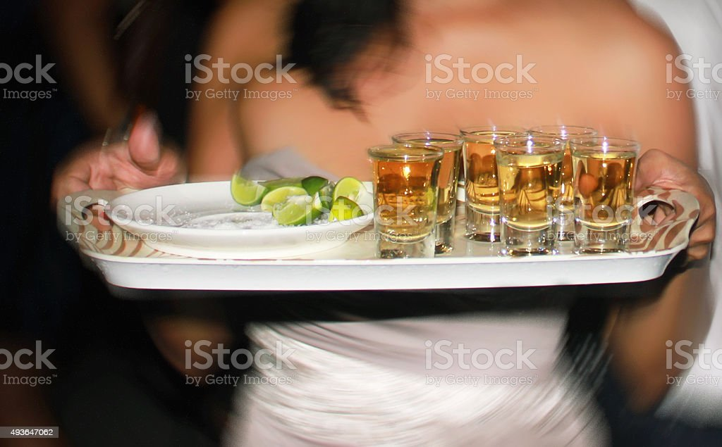 Woman serving tequilla shot stock photo