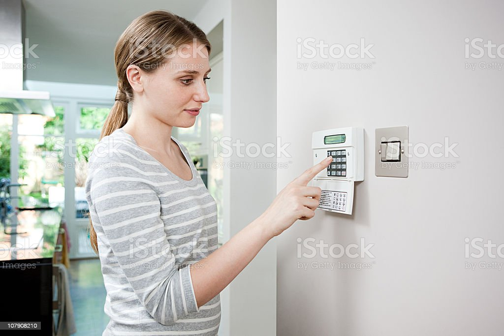 Woman setting burglar alarm stock photo