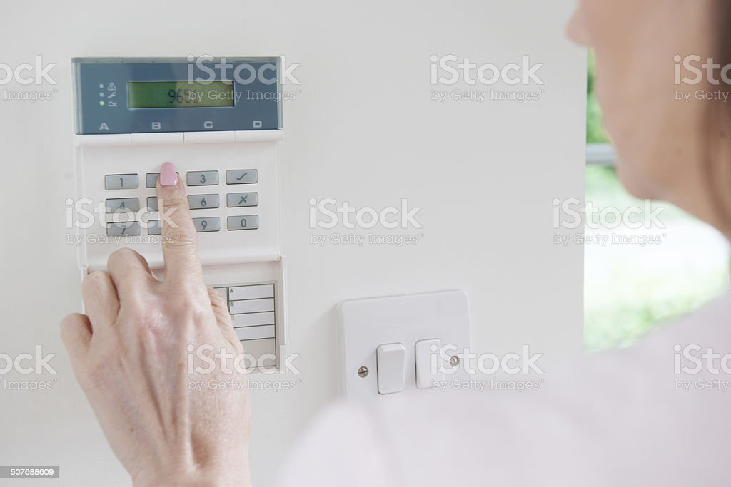 Woman Setting Control Panel On Home Security System stock photo