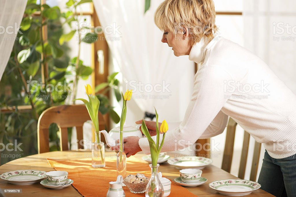 Woman setting the table for tea of coffee time stock photo
