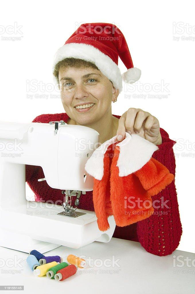 woman sewing a fur coat for Santa Claus royalty-free stock photo