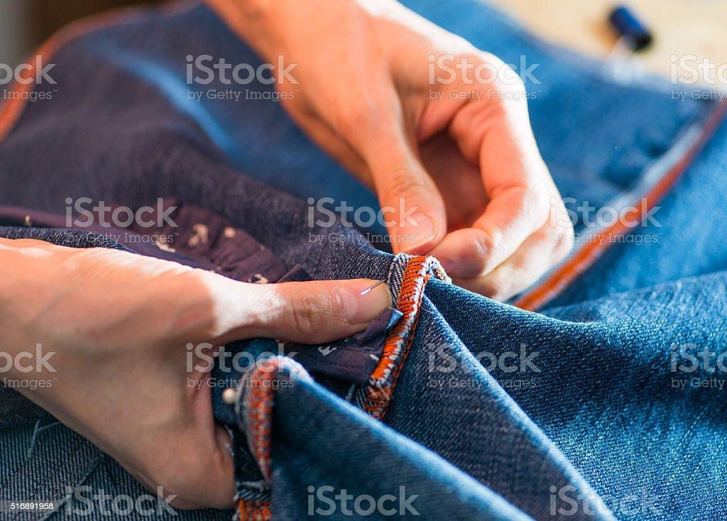 woman sewing denim stock photo