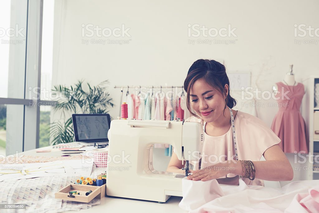 Woman sewing stock photo