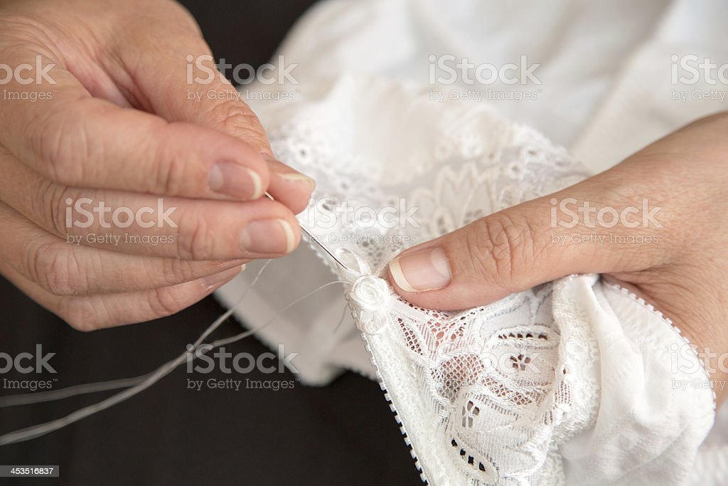 Woman sewing ribbon and rose to lingerie royalty-free stock photo