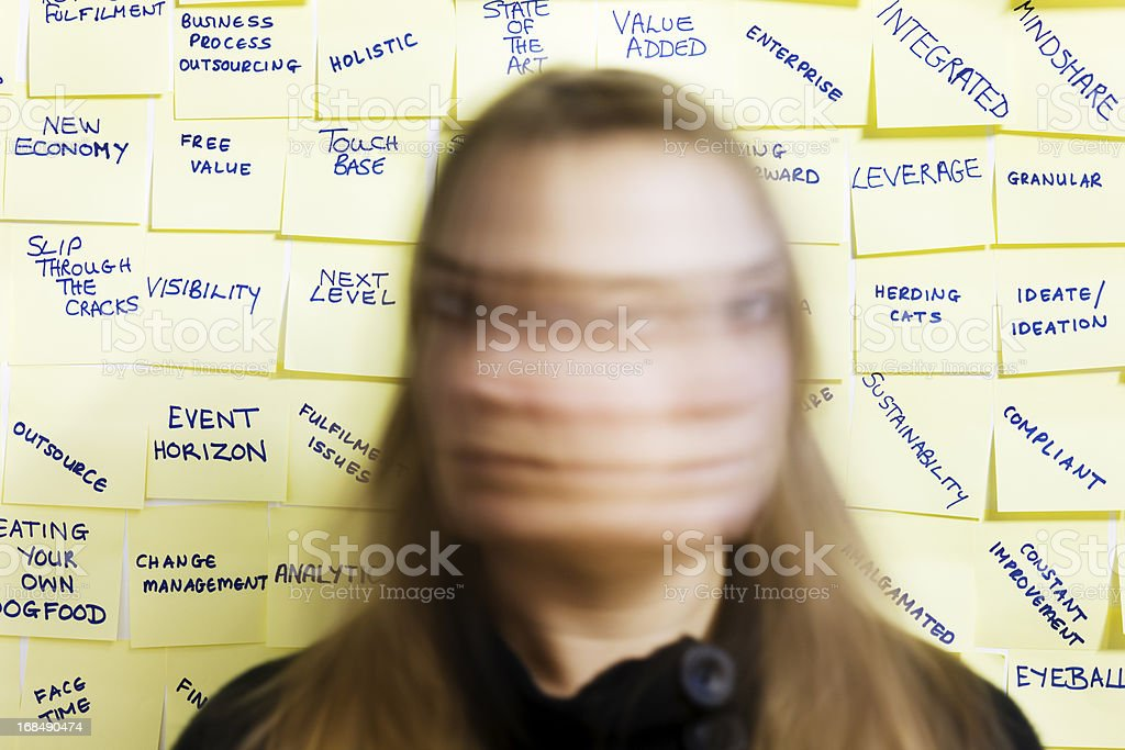 Woman shakes head in blurred motion against business buzzwords stock photo