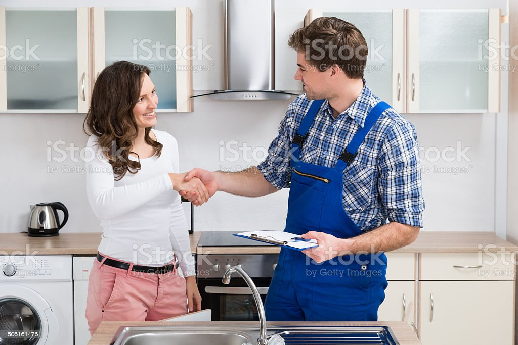 Woman Shaking Hands To Plumber stock photo