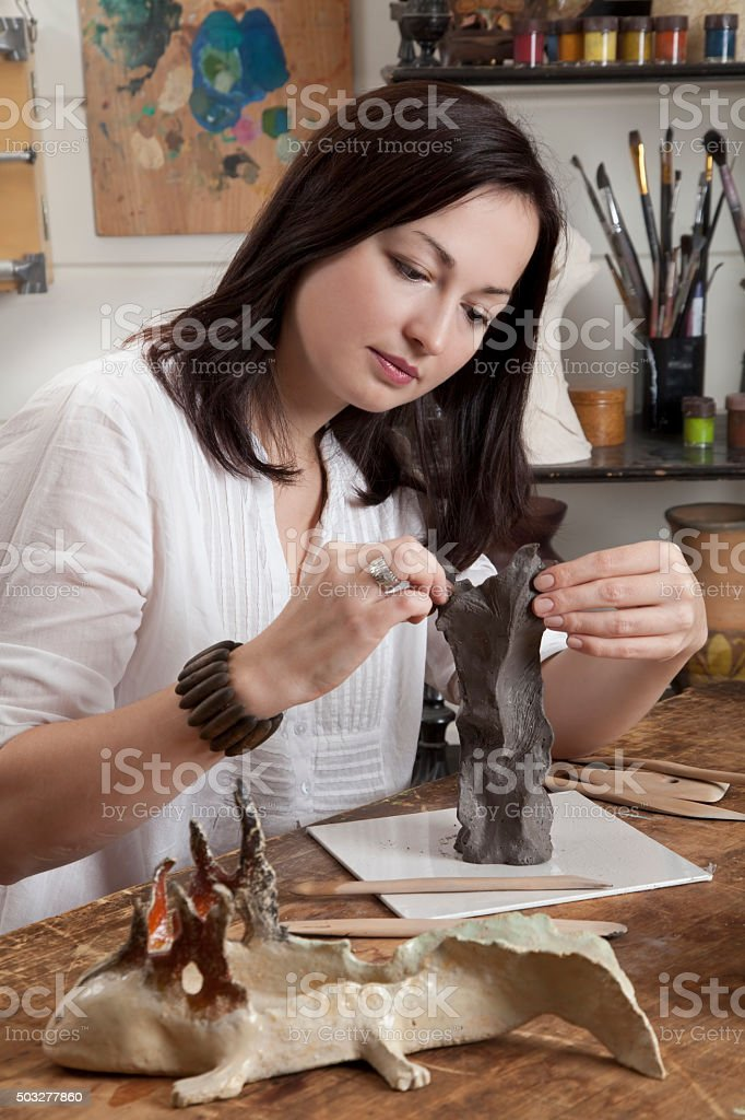 Woman shaping clay sculpture stock photo