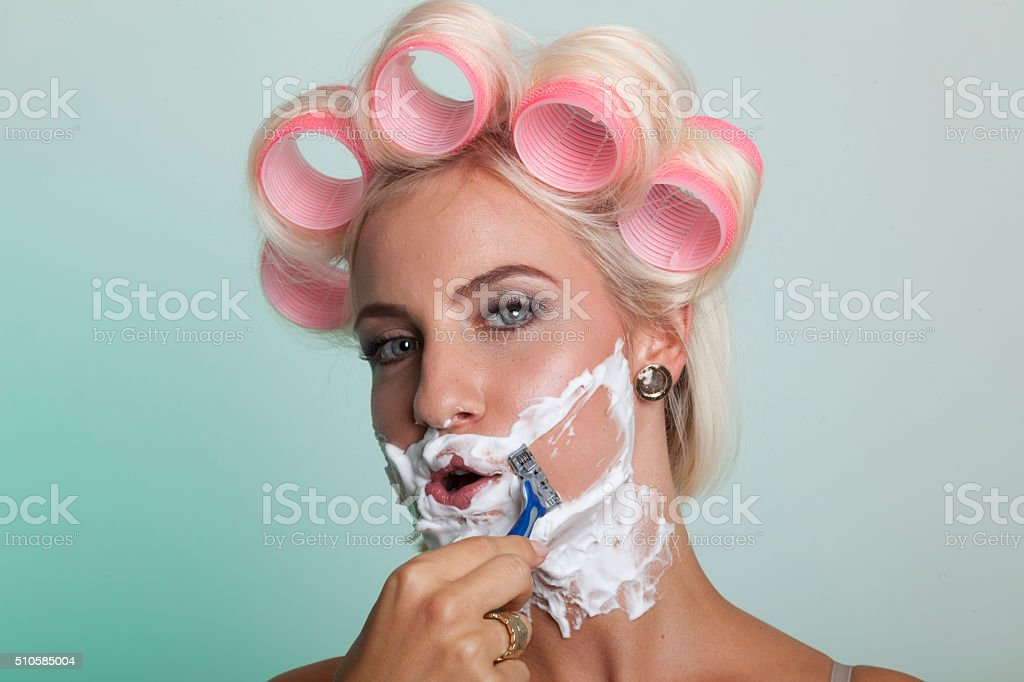 Woman shaves her beard stock photo