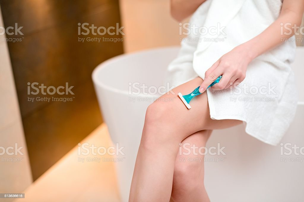 Woman shaving legs with razor blade in bathroom stock photo
