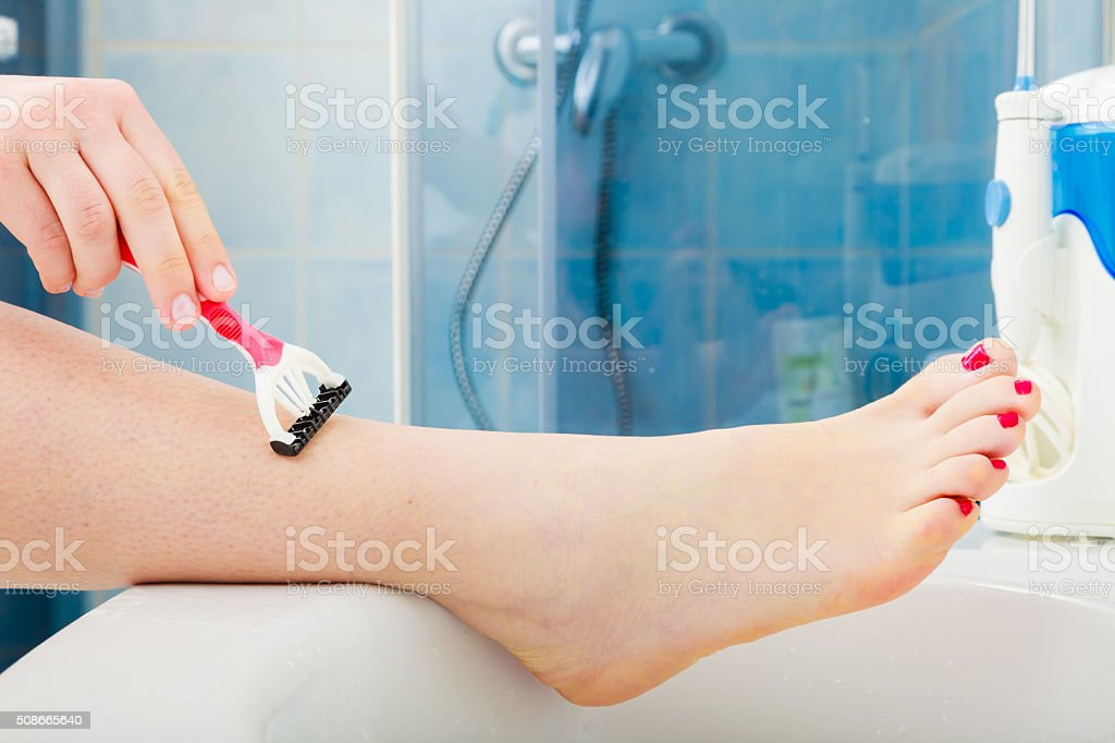 Woman shaving legs with razor in bathroom stock photo