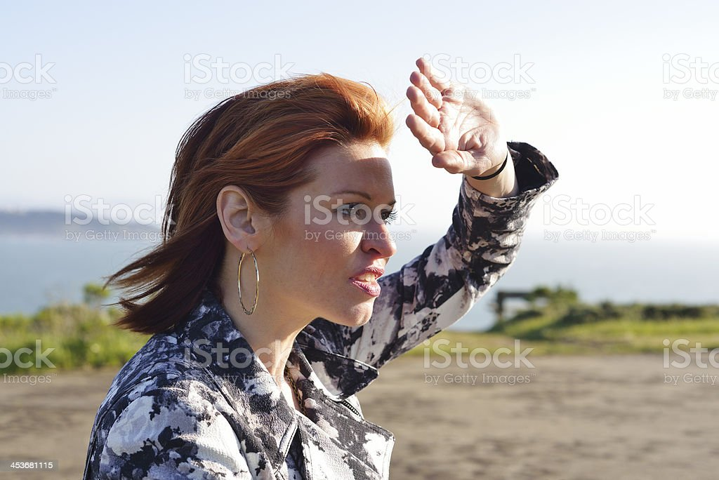 Woman shielding her eyes stock photo