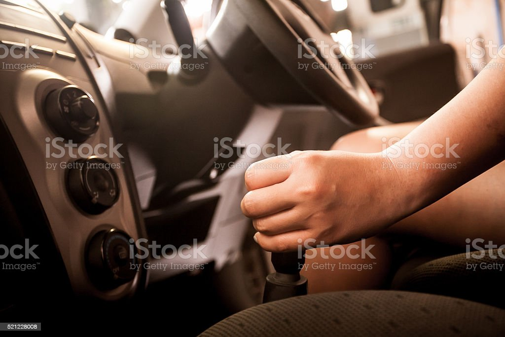 woman shifting gears on gearbox in car stock photo