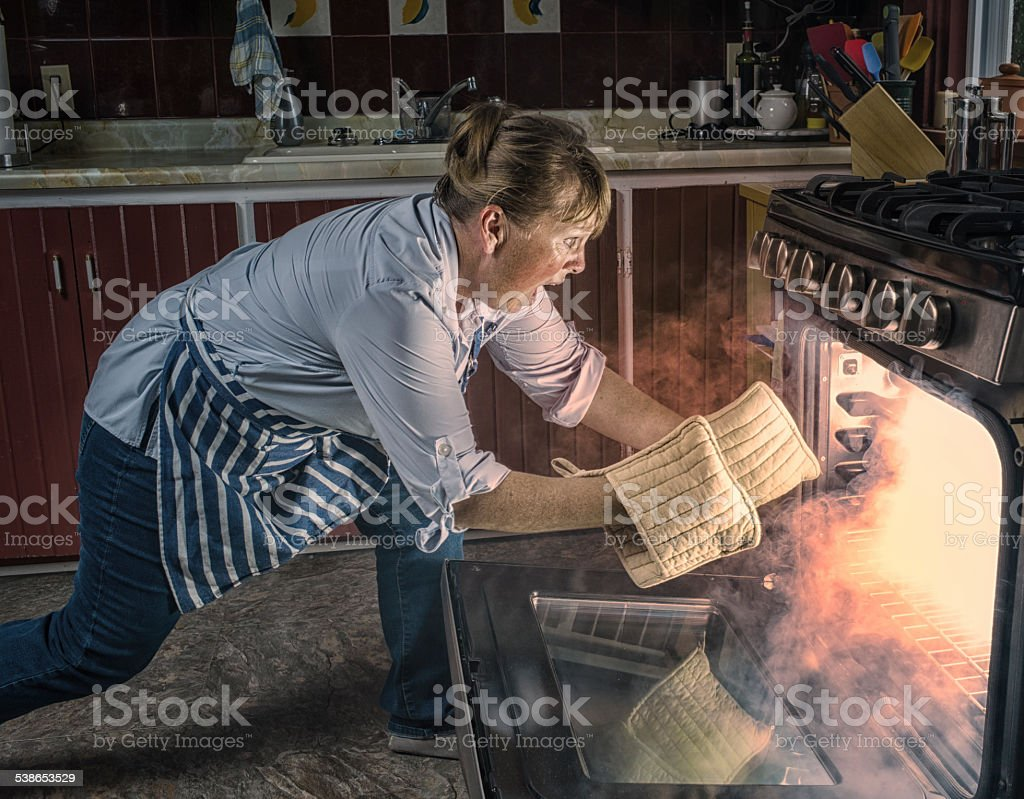 Woman  Shocked  at Oven Fire While Cooking in the Kitchen. stock photo