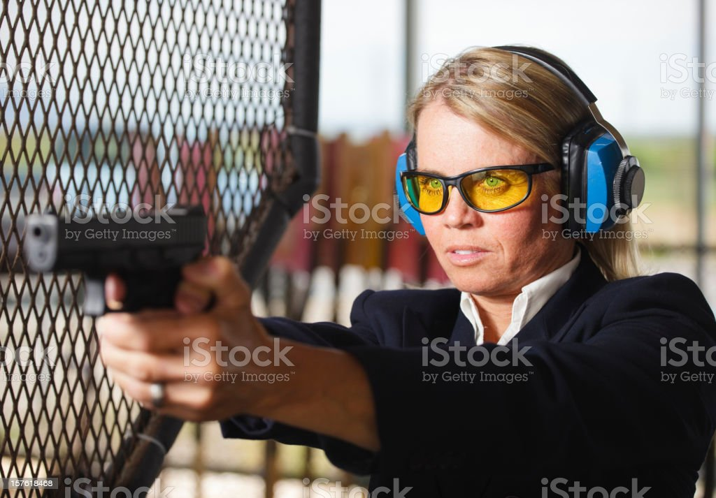 A woman in business clothing standing at the shooting range holding a...