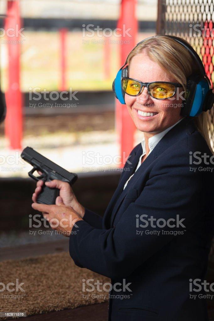 A woman standing at the shooting range holding a handgun.