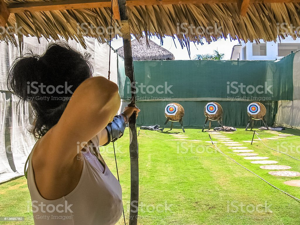 Woman shooting with bow stock photo