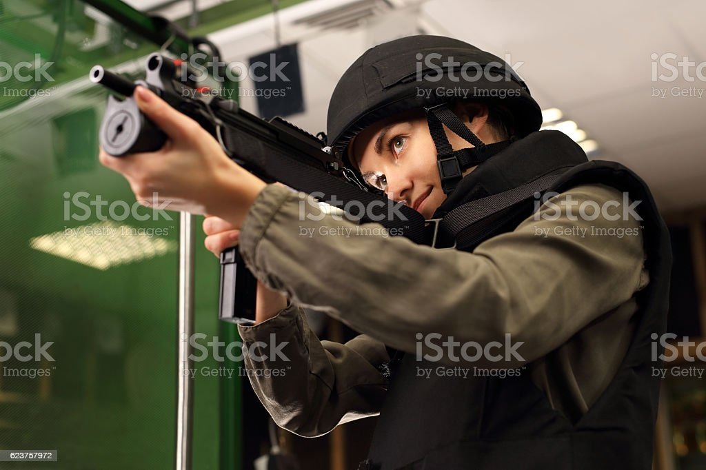 Woman shoots a rifle at the shooting range stock photo
