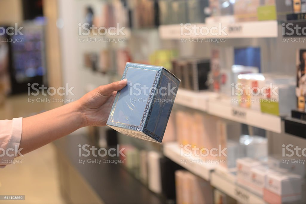 Woman holds a blue box of cosmetics in a store.