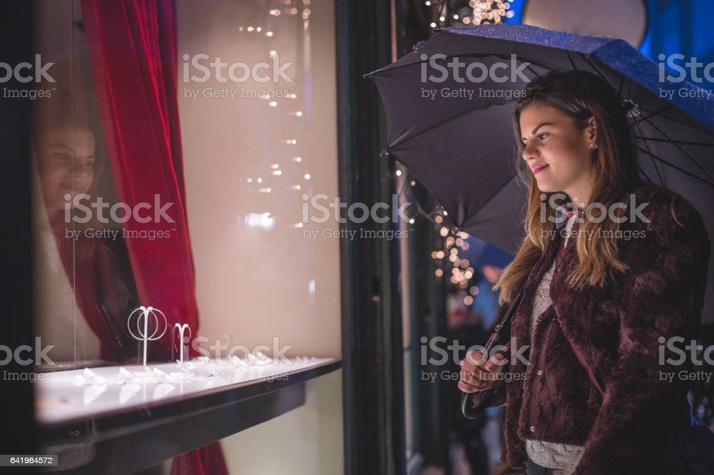 Woman shopping a jeweler on a rainy shiny night stock photo