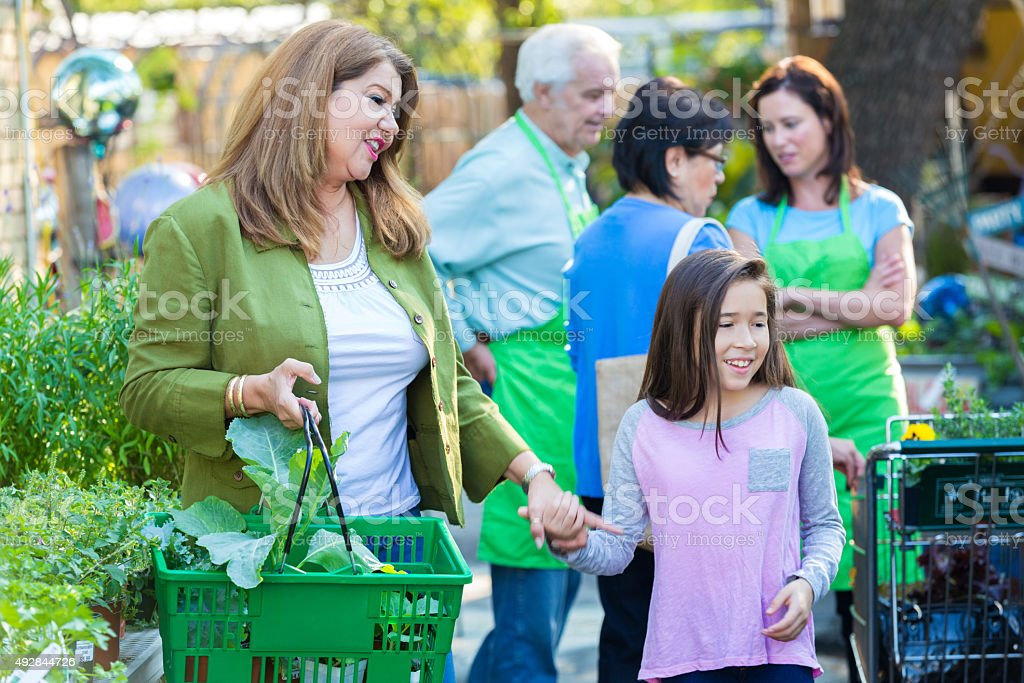 Woman shopping at gardening store with young daughter stock photo