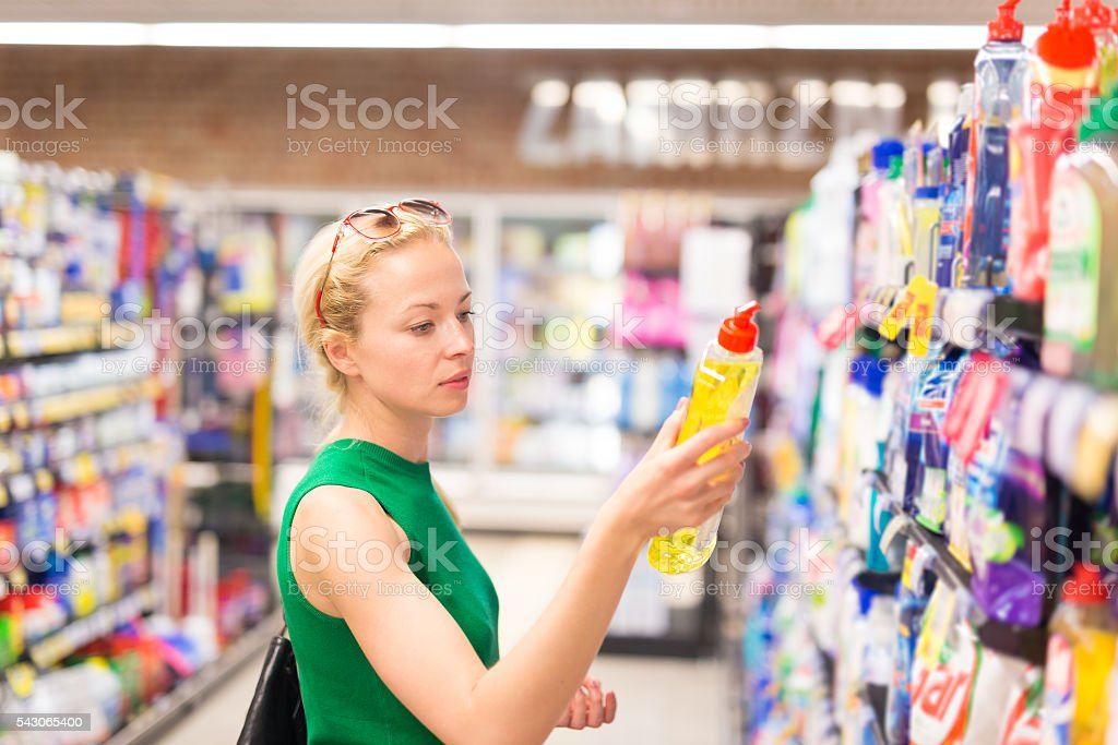 Woman shopping cleaners at supermarket. stock photo