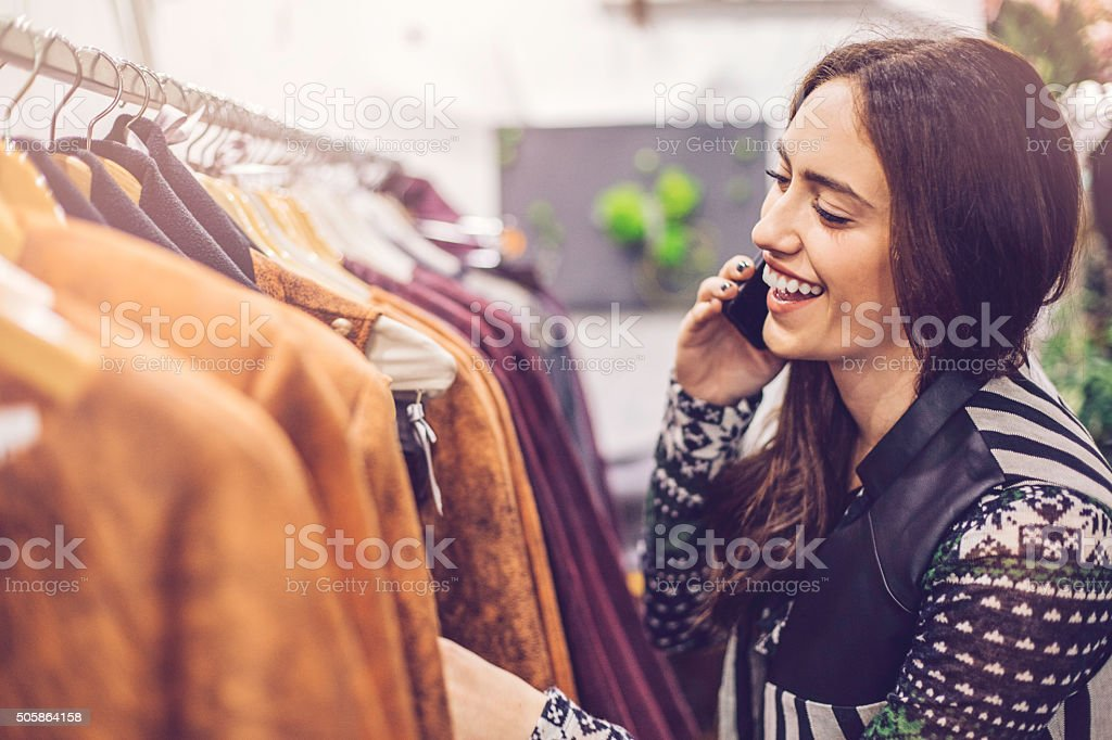 Woman shopping clothes and talking on the phone stock photo
