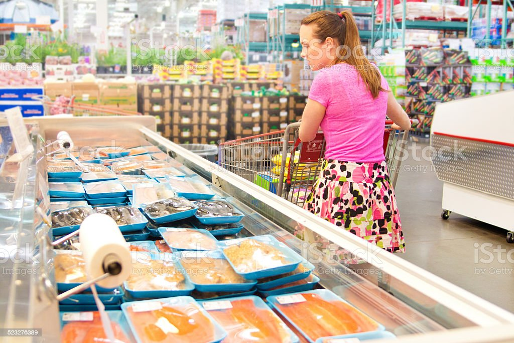 Woman Shopping for Fresh Fish Seafood in Supermarket Retail Store stock photo