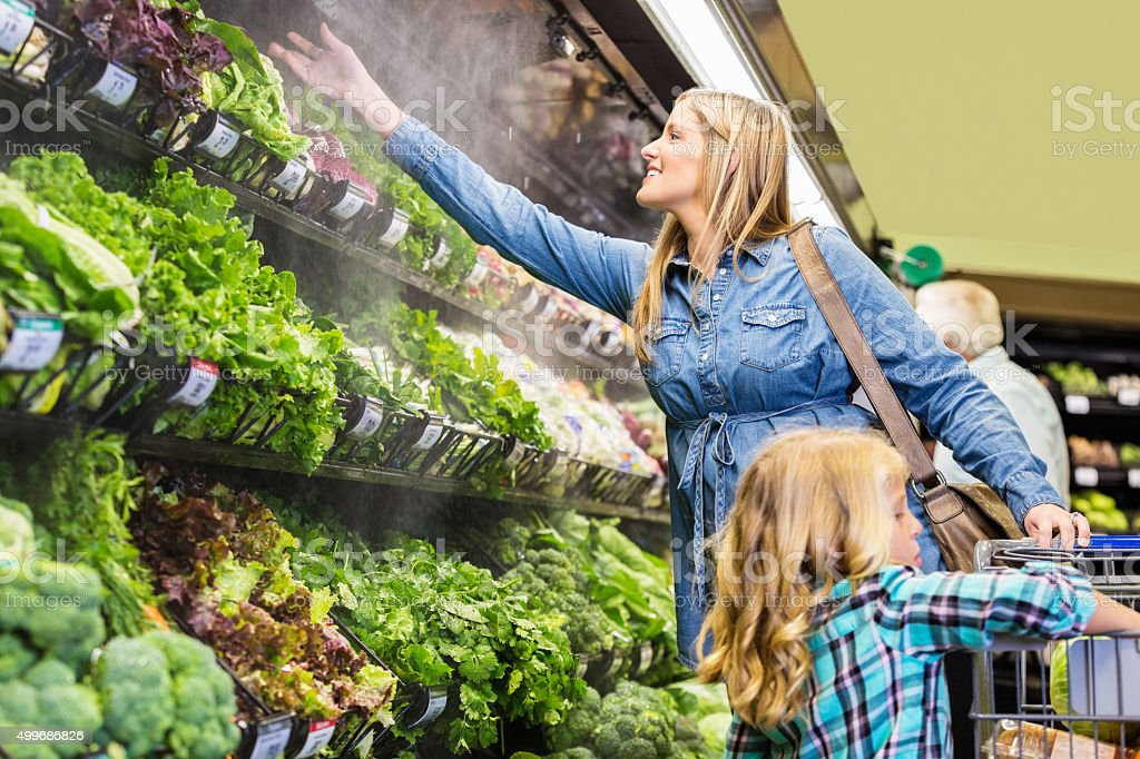 Woman shopping for fresh produce in grocery store stock photo