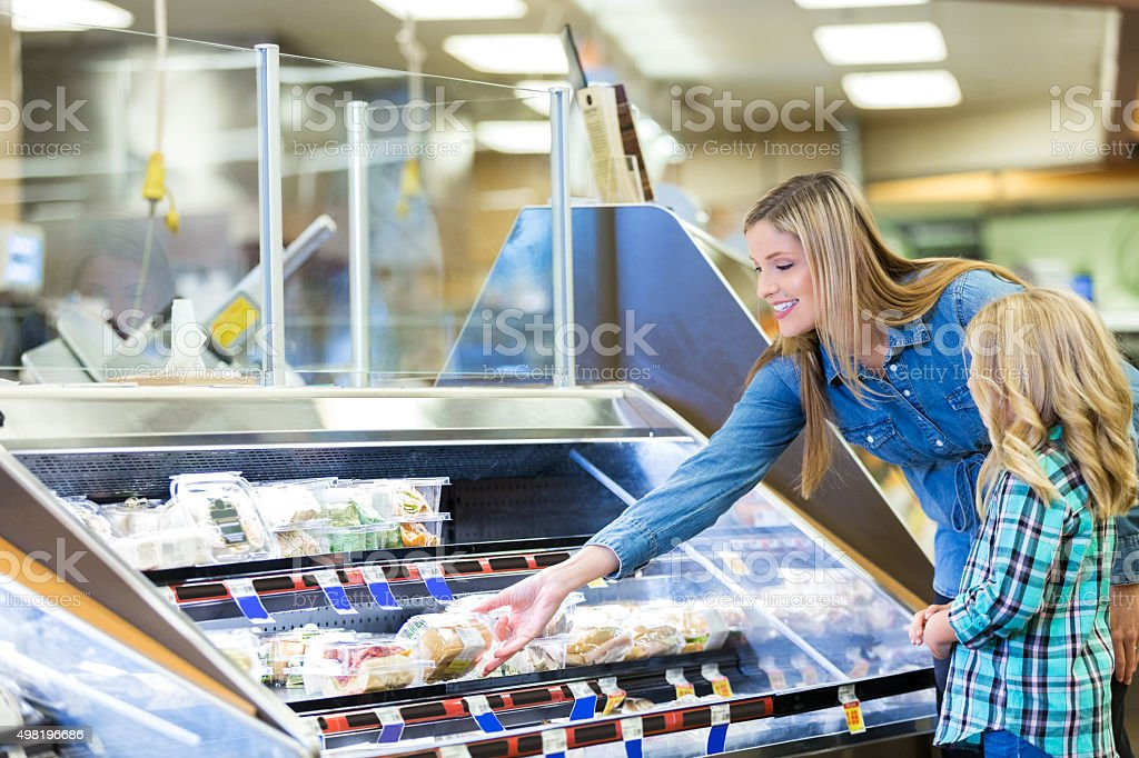 Woman shopping for prepared foods in deli with daughter stock photo