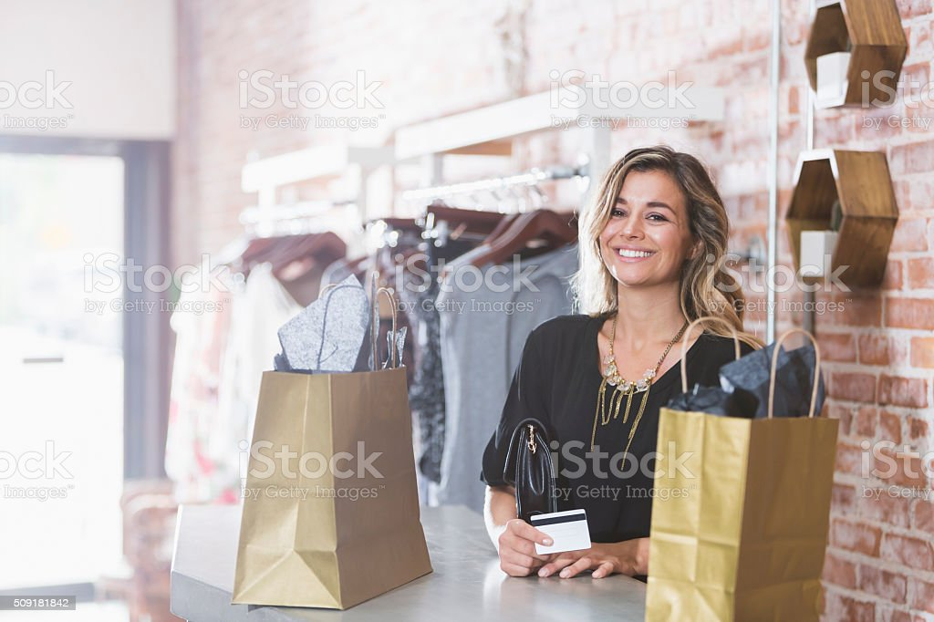Woman shopping in clothing store paying with credit card stock photo