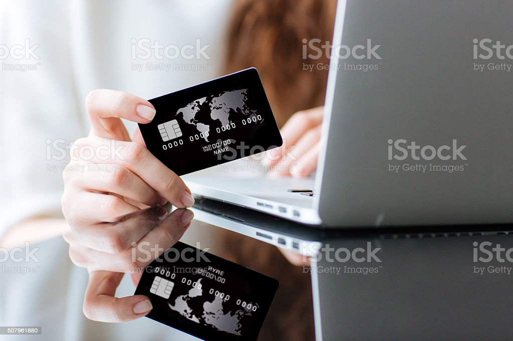 Woman shopping online on laptop computer with credit card stock photo