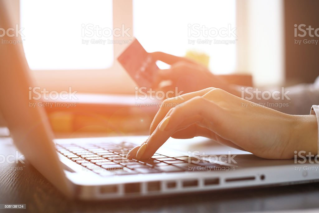 Woman Shopping Online Using Laptop With Credit Card stock photo