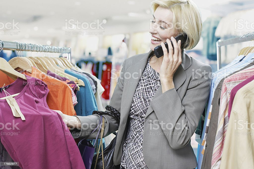 Woman shopping while on cellular phone royalty-free stock photo