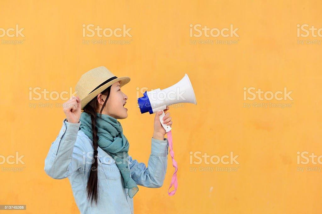 Woman shouting through megaphone stock photo