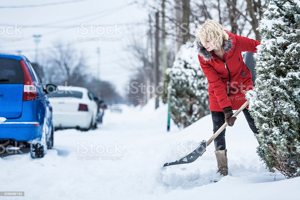 Woman Shoveling her Parking Lot stock photo
