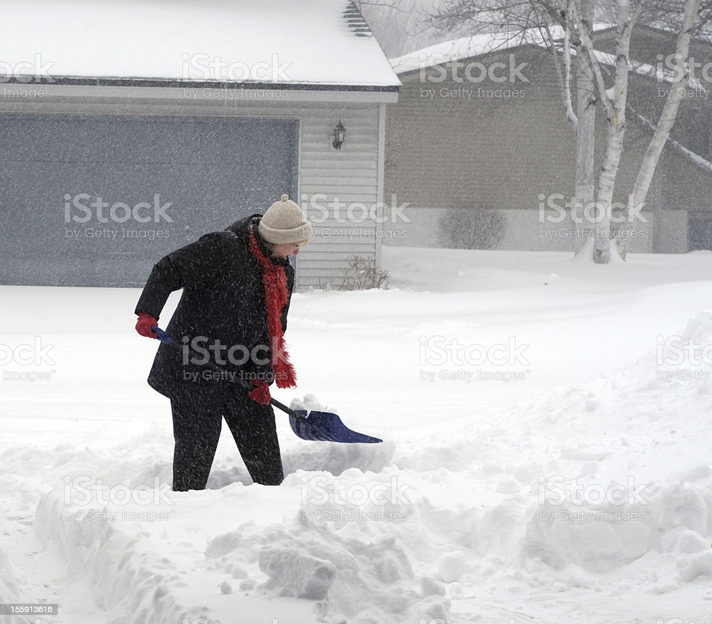Woman Shoveling Path in Snow stock photo