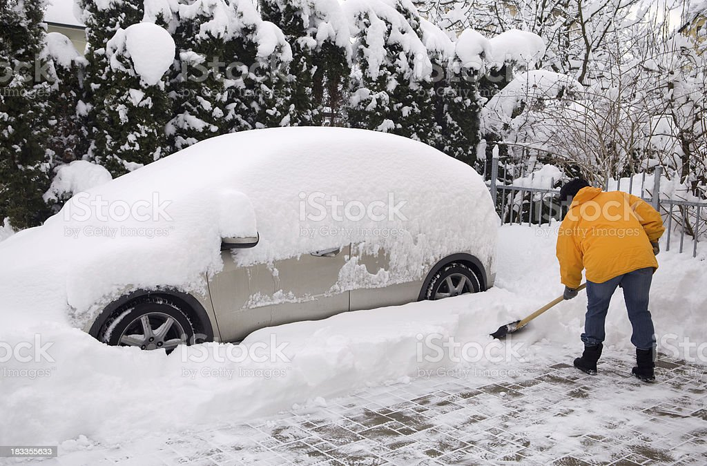 Woman shovelling around snow covered car stock photo
