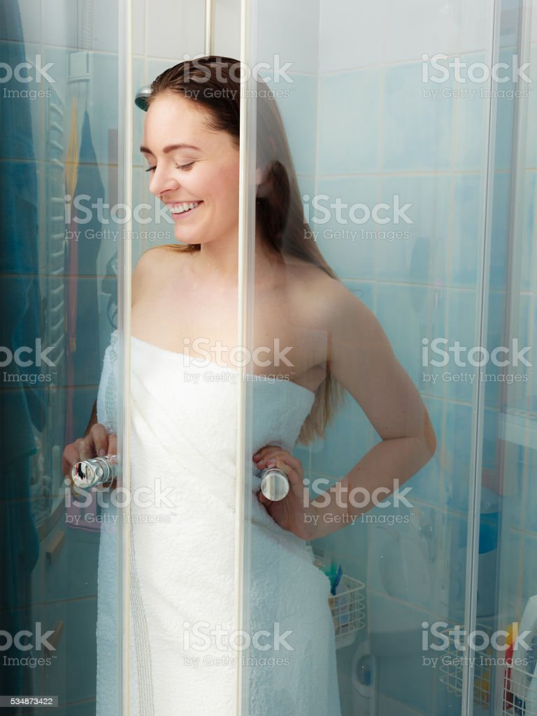 Woman showering in shower cabin cubicle. stock photo