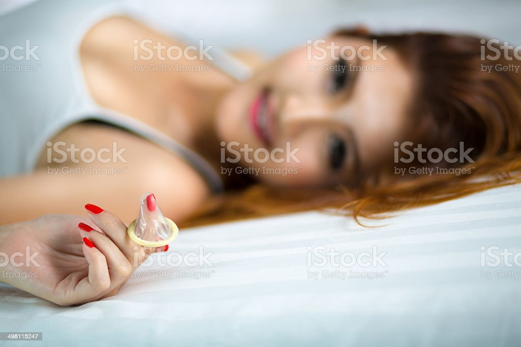 Woman showing a condom on bed stock photo