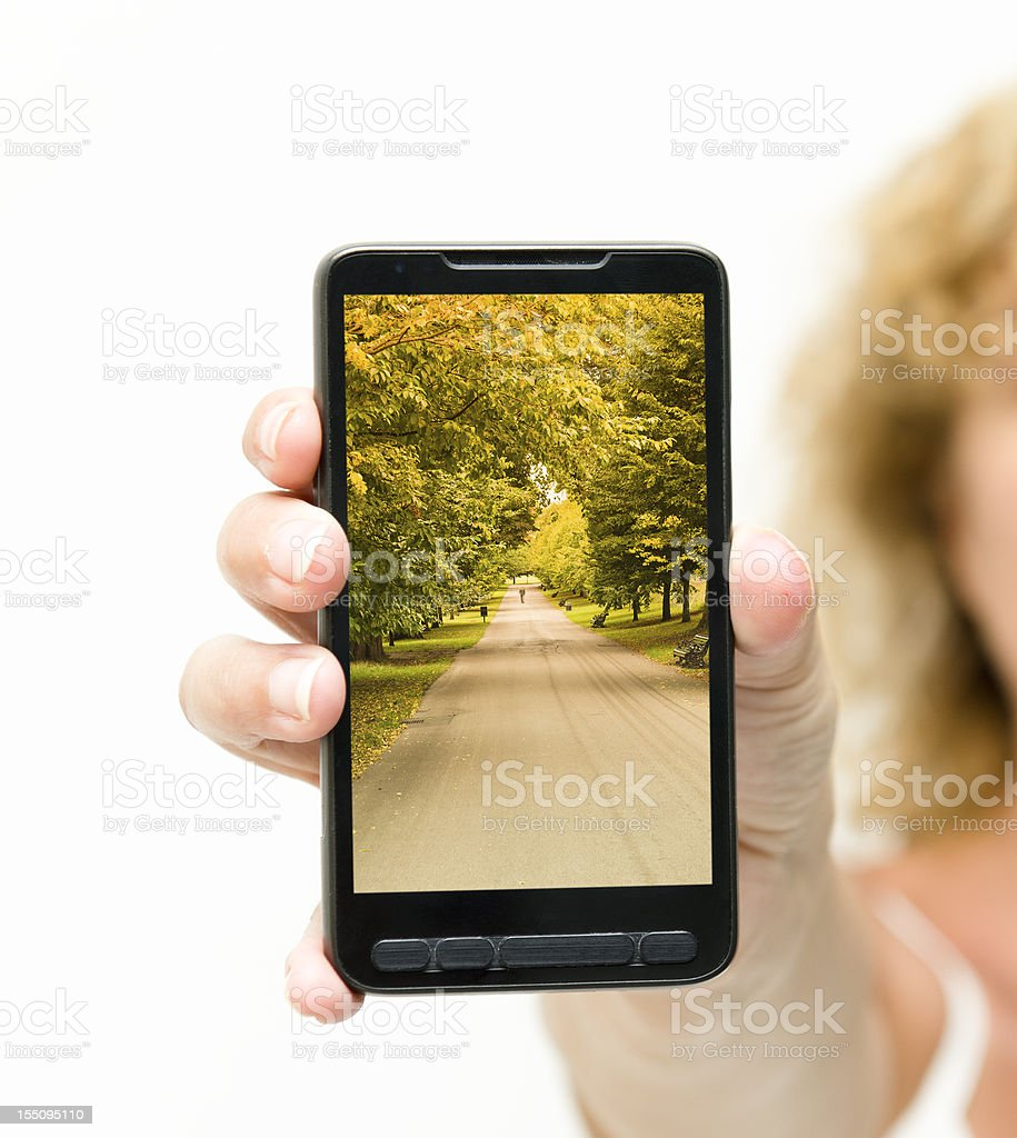 Woman showing a contemporary smart phone with London park Image royalty-free stock photo