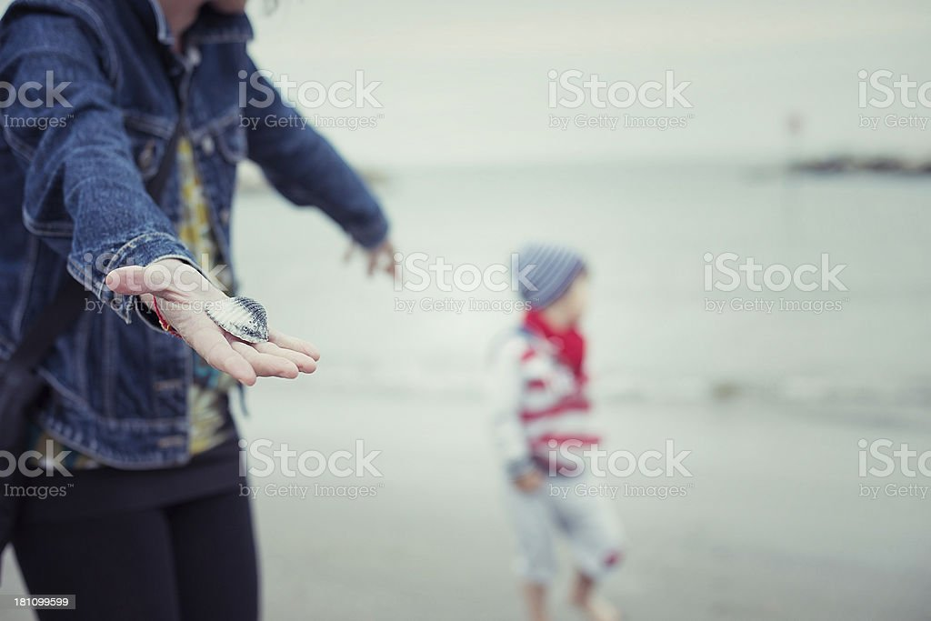 Woman Showing a Shell Child in the Background stock photo