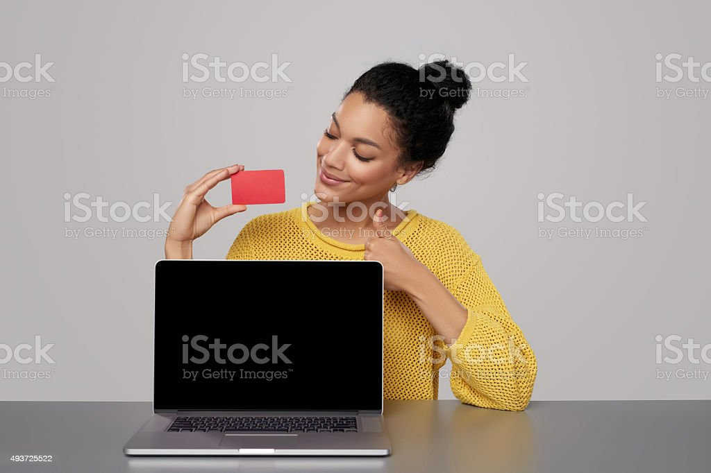 Woman showing black laptop screen and credit card stock photo