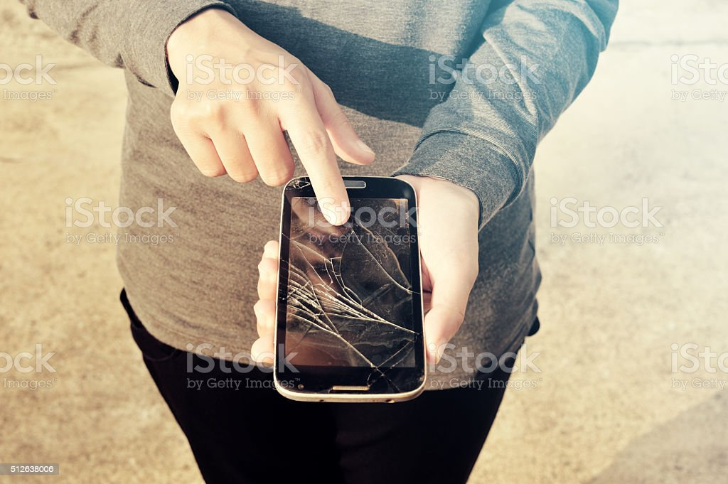 Woman showing broken smartphone with crashed screen stock photo