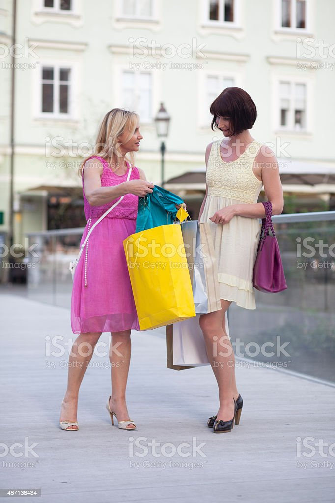 Woman showing cloth to her friend stock photo