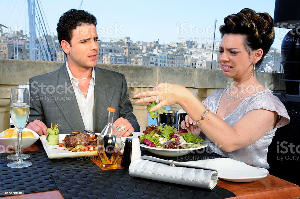 A woman showing disgust at a date with a disappointed man royalty-free stock photo