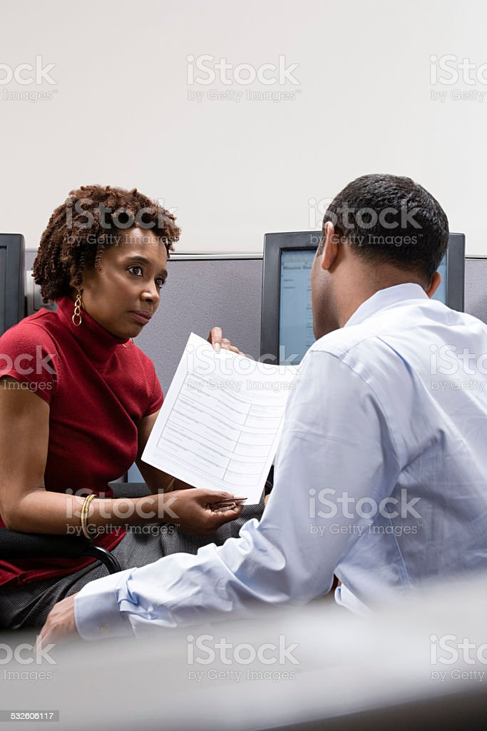 Woman showing form to colleague stock photo